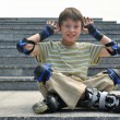 The jolly boy with roller blades sitting at the granite pavement — Stock Photo