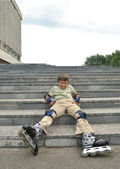 The boy with roller blades rests on the stairs — Fotografia Stock