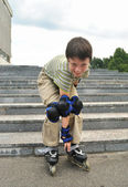 The boy with roller blades looks into the objective of camera — Stock Photo