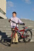 男孩拿着他的红色自行车 — 图库照片