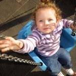 Portrait of girl swinging on swing. — Stock Photo