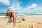Young woman sitting on a sand — Stock Photo