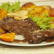Beef steak with caramel orange chips — Stock Photo