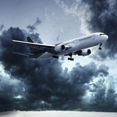 Jet in dramatic stormy sky — Stock Photo
