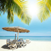 Table, chairs and parasol at the tropical beach — Stock Photo