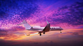 Private jet maneuvering in a spectacular sunset sky — Stok fotoğraf