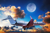 Luxurious private jet maneuvering in a sky at sunrise time — Stock Photo