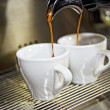 Two cups of coffee in front of coffee machine. — Stock Photo