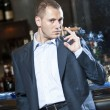 Businessman smoking cigar next to bar stand — Stock Photo #16223249