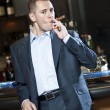 Businessman smoking cigar next to bar stand — Stock Photo #16223255
