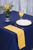 An elegant dining table setting with a dark blue cloth and a yellow napkin. — Stock Photo