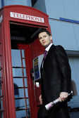 Successful yang man in business suit posing in front of vintage phone booth — Stock Photo