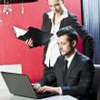 Two business persons posing in office with lap top — Stock Photo