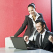 Two business persons posing in office with lap top — Stock Photo #17976603