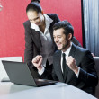 Two business persons posing in office with lap top — Stock Photo #17976719