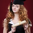 Studio portrait of beautiful curly female graduating student dressed in cup and gown — Stock Photo