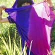 Stock Photo: Beautiful young gipsy womin purple dress, against green of summer park