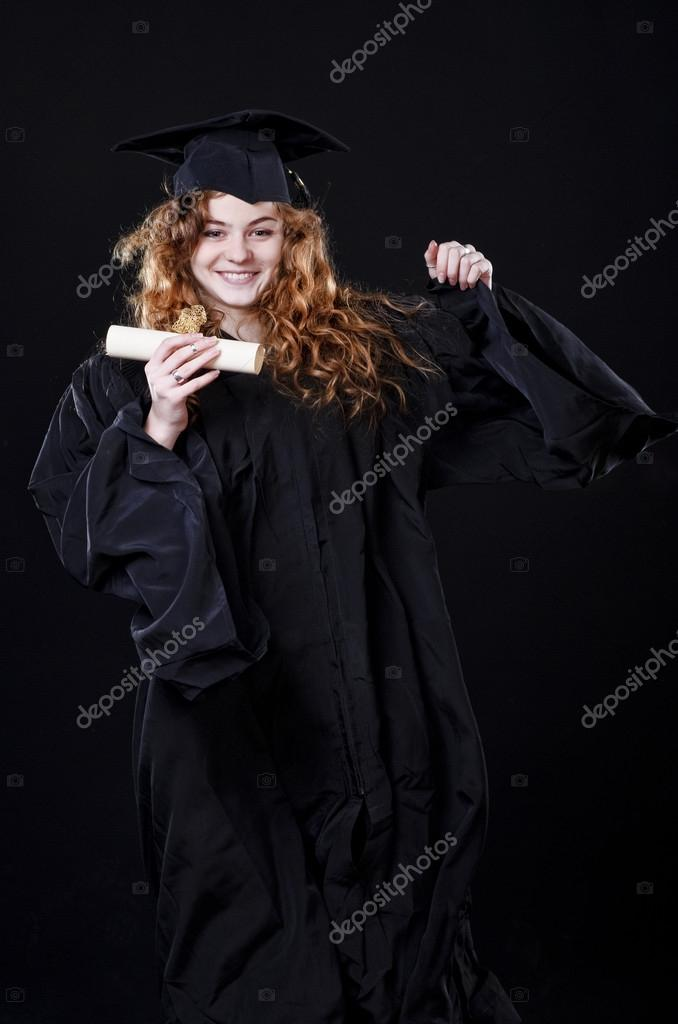 Studio portrait of beautiful curly female graduating student dressed in cup and gown — Stock Photo #18547355