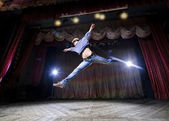 Modern ballet style male dancer performs on high lighted stage — Stock Photo