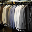Raw of different colors man's jackets hanging on apparel. — Stock Photo #19188779
