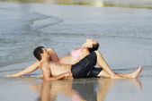 Couple with pregnant woman relaxing on the beach. — Stock Photo