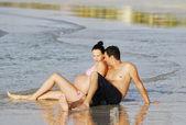 カップルはビーチでリラックスした妊娠中の女性 — ストック写真