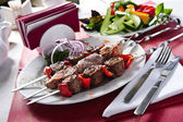 Plate of shish kebab arranged on table — Stock Photo