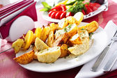 Plate of baked potatoes cooked on skewers — Stock Photo