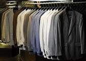 Raw of different colors man's jackets hanging on apparel. — Stockfoto
