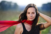 Outdoor portrait of yang beautiful woman with red scarf — Stock Photo