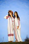Outdoor portrait of yang and beautiful Slav girls dressed traditional way — Stock Photo