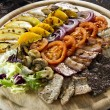 Plate of different kinds grilled meat with fruits and vegetables — Stock Photo