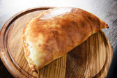 Wooden plate of traditional Italian calzone — Stock Photo
