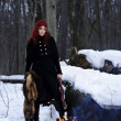 Portrait of red haired beautiful and wild yang woman the hunter in the winter gloomy forest. — Stock Photo
