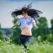 Stock Photo: Pretty young European woman jumping on green field
