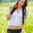 Stock Photo: Beautiful brunette poses among green summer field