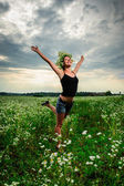Yang Slav woman in flower wreath posing among green field — Stock Photo
