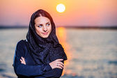 Women dressed middle eastern way poses on sunset background — Stock Photo