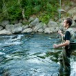 A fisherman fishing on a river — Stock Photo #13173015