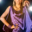 Young woman posing in purple dress, studio shot with lights in b — Stock Photo