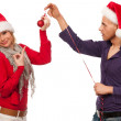 Girl and man with santa hat and red christmas bauble ornament — Stock Photo