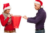 Girl and man with santa hat fighting for a present — Stock Photo