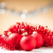 Foto de Stock  : Christmas ornaments - red baubles with shiny tape in background