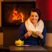Attractive young woman drinks tea in a warm room near fireplace with teapot on a table — Stock Photo