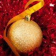 Christmas ornaments - golden bauble with shiny tape in backgroun — Stock Photo