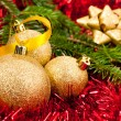 Christmas ornaments - golden baubles with shiny tape in backgrou — Stock fotografie