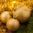 Christmas ornaments - golden baubles with shiny tape in backgrou — Stock Photo
