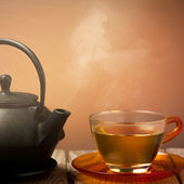 Teapot and a cup of tea on an old wooden table - hot steam smoki — Stock Photo