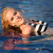 Attractive blonde girl in bikini swimwear in swimming pool on late summer afternoon — Stock Photo