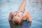 Attractive blonde girl in bikini swimwear in swimming pool on late summer afternoon — Stock Photo
